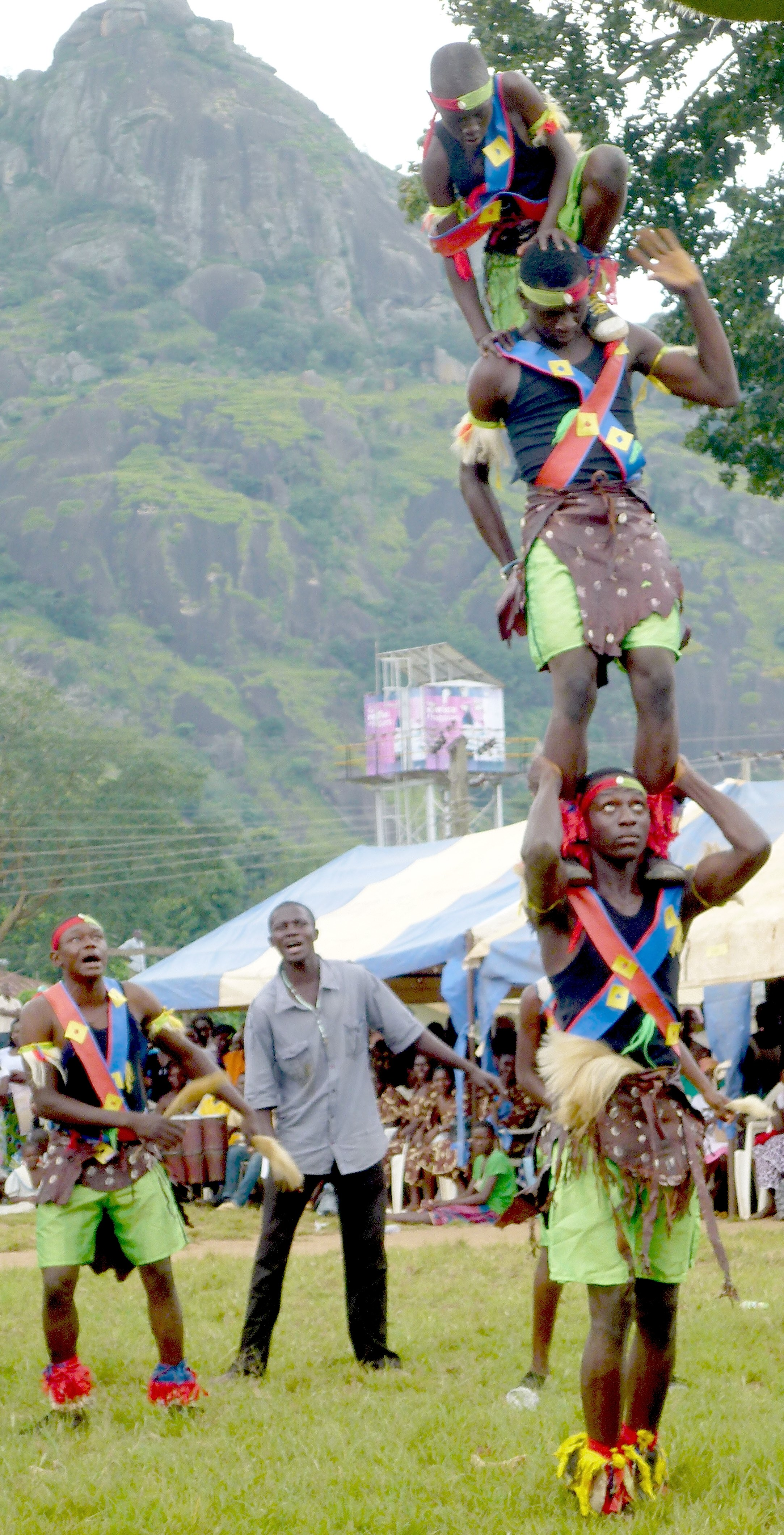 Several people balancing on each other to form a very precarious looking human tower at the Gworog traditional festival 2014